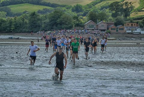 A photo of lots of runners taking part in The Mud Race across the River Teign at low tide
