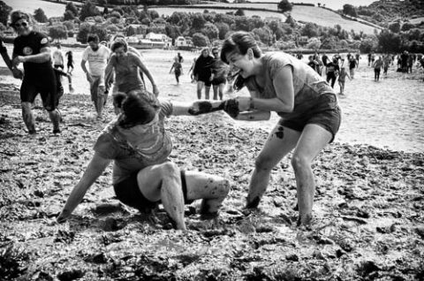 A black and white photo of two ladies having fun running in The Mud Race across the River Teign at low tide