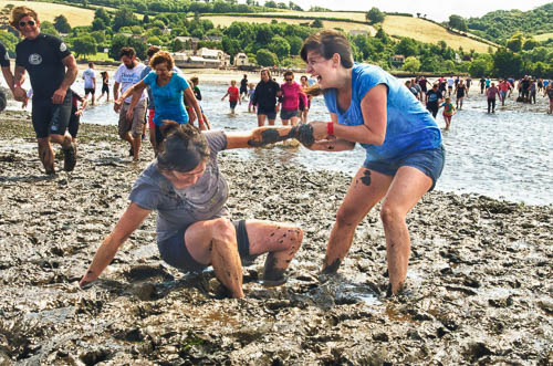 A photo of two ladies having fun running in The Mud Race across the River Teign at low tide