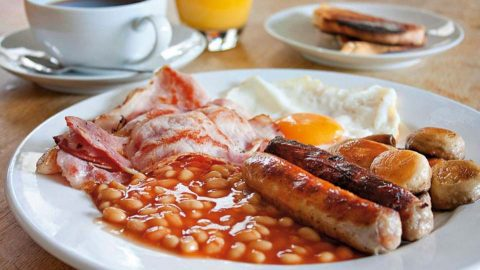 Photo of Cooked breakfast: bacon, baked beans, sausages, mushrooms and fried egg.