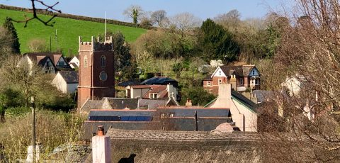 Photograph of All Saints church, Combeinteignhead, in the distance over the rooftops of the village