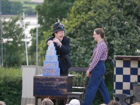 Photo of two actors performing on stage during a Miracle Theatre performance on Hearn Field
