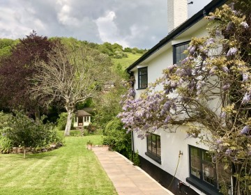 Photo of a whitewashed cottage with wisteria