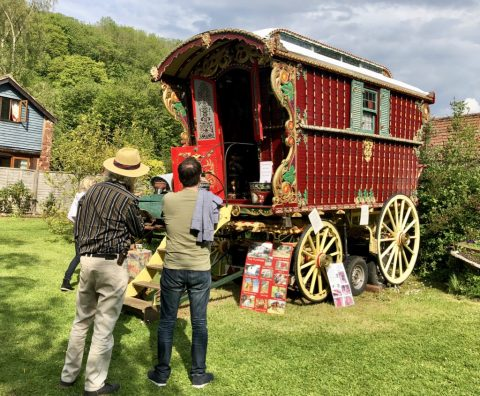 Photo of a group of people admiring a restored Romany gypsy caravan in a garden setting