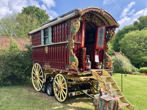Photo of a restored Romany gypsy caravan in a garden setting