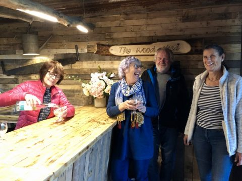 A photo of 4 local residents celebrating the opening of The Wood Shed, the new bar facility in Hearn Field Pavilion.