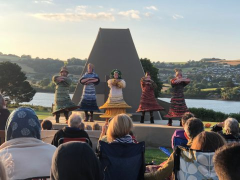 A photo of 5 actors on stage performing a play called The Perfect World with the River Teign in the background