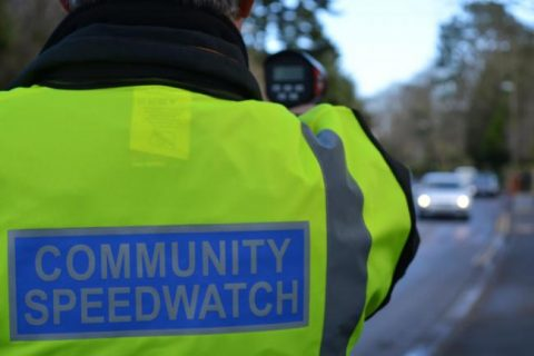 Image of a speed watch volunteer wearing a hi-vis jacket with the words Community Speedwatch on the back